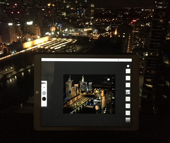 Ipad with view and digital illustration of Melbourne city at night by Alison Davies